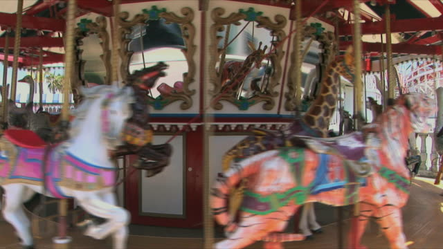 ms empty carousel spinning in amusement park, belmont park, san diego, california, usa - 回転遊具点の映像素材/bロール