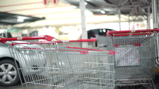 vídeos de stock, filmes e b-roll de carrinho vazio no estacionamento de supermercado em situação covid-19 - parking