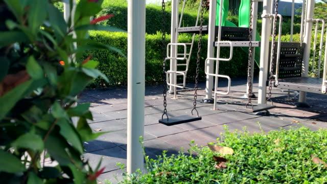 vídeos de stock e filmes b-roll de empty chain swings at a playground in the park. - equipamento de parque infantil