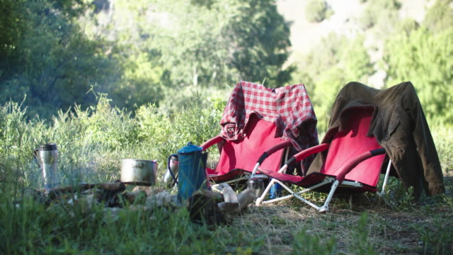 empty chairs around a campfire in the mountains - equipment点の映像素材/bロール