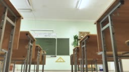 Empty Classroom with Wooden Desks and Green Chalkboard at School