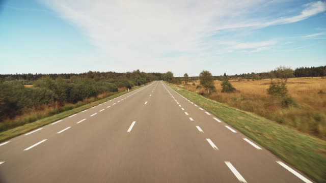 empty country road amidst field against sky - empty road stock videos & royalty-free footage
