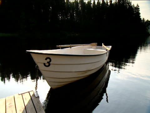 Empty cream colored rowing boat moored by jetty on forest lake