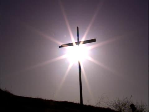 empty cross on a hill with the sun behind - 許し点の映像素材/bロール