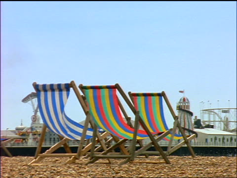 3 empty deck chairs on rocky beach at Brighton / Victorian Palace Pier in background / England