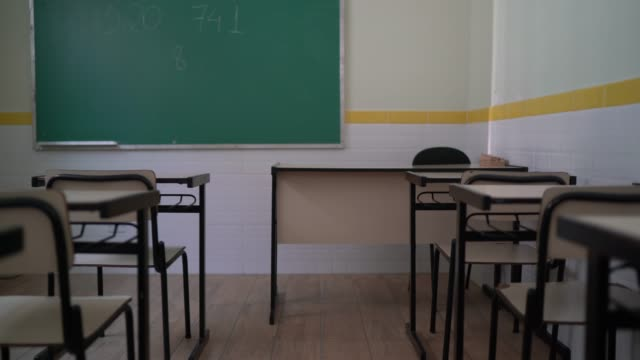 empty desks sit inside a vacant classroom - school theme - corridor stock videos & royalty-free footage