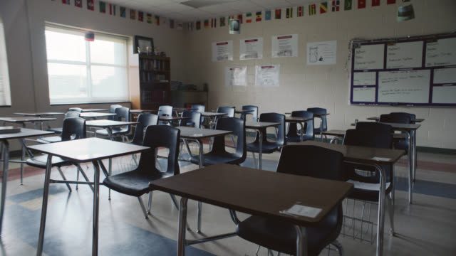 empty desks sit inside a vacant classroom - aula video stock e b–roll