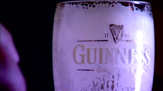 CU Empty draught beer pint glass w/ Guinness name harp logo on side glass coated inside w/ stout foam male hand lifting glass out of frame