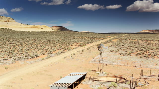 vídeos de stock, filmes e b-roll de empty enclosures and still windpump on abandoned farm in utah - drone shot - terreno extremo
