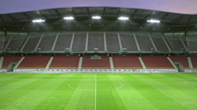 pan empty football stadium in the evening - football pitch stock videos & royalty-free footage