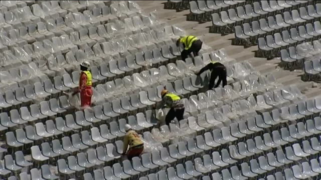 empty football stadium workmen removing plastic sheeting from seats in stands soccer city reporter to camera - soweto stock videos and b-roll footage