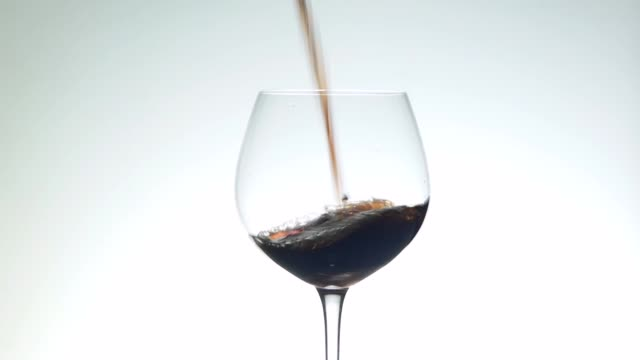 vídeos de stock e filmes b-roll de empty glass being filled with red wine on a white background. - copo vazio