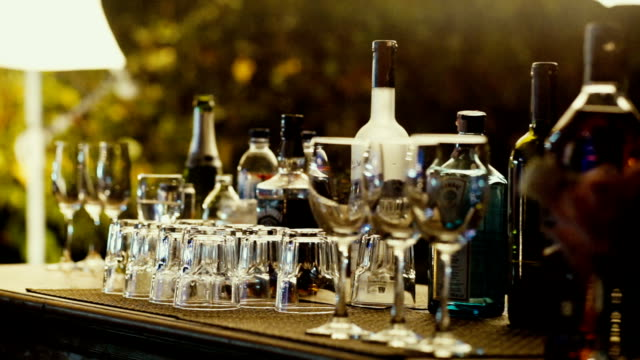 Empty glasses and alcohol drink on bar counter in outdoor party at night.