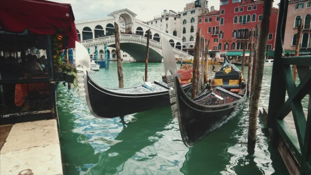 empty gondolas in front of rialto bridge. the bridge is a famous international landmark in venice, italy, jib - canal stock videos & royalty-free footage
