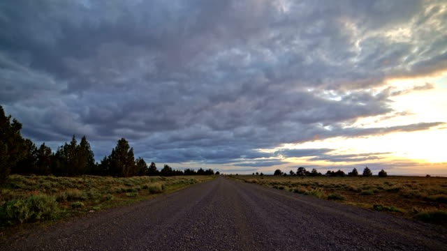 Empty gravel road at sunset with clouds in the desert South Steens Mountain near Malheur National Wildlife Refuge