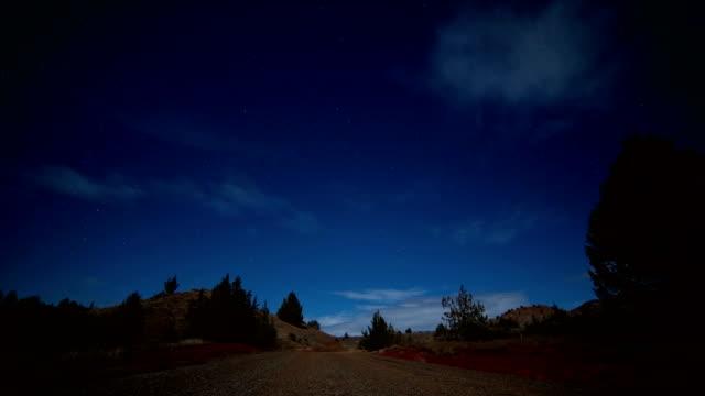 empty gravel road under the moon and stars night near painted hills - セージブラッシュ点の映像素材/bロール