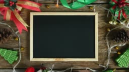 Empty green board placed on wooden table decorated with Christmas decorations. Top view