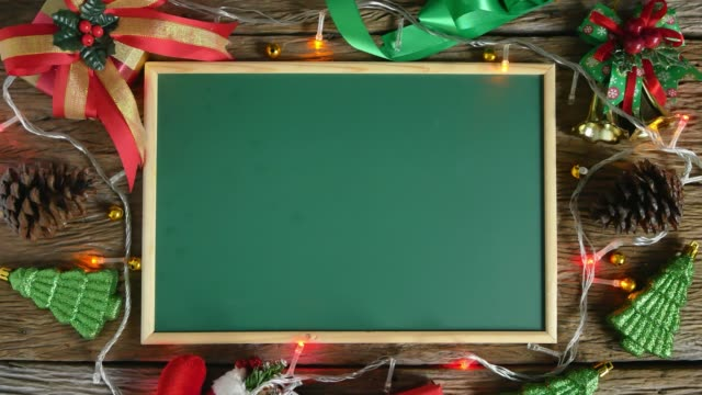empty green board placed on wooden table decorated with christmas decorations. top view - picture frame stock videos & royalty-free footage
