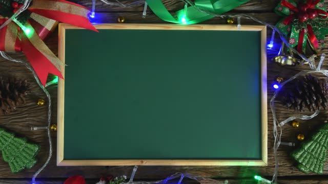 empty green board placed on wooden table decorated with christmas decorations. top view - greeting card stock videos & royalty-free footage