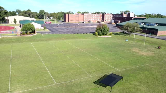empty high school football field and parking lot - sportplatz stock-videos und b-roll-filmmaterial