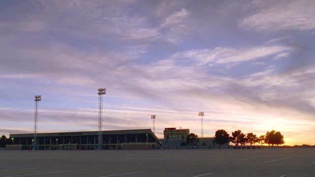 ws empty high school football stadium at sunset / odessa, texas - american football pitch stock videos & royalty-free footage