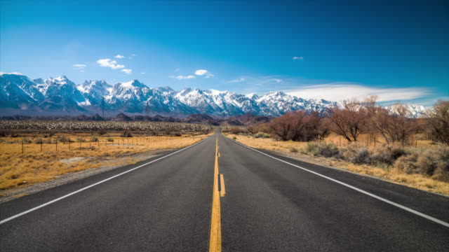 empty highway in idyllic landscape with sierre nevada mountains in the background, california - western usa stock videos & royalty-free footage