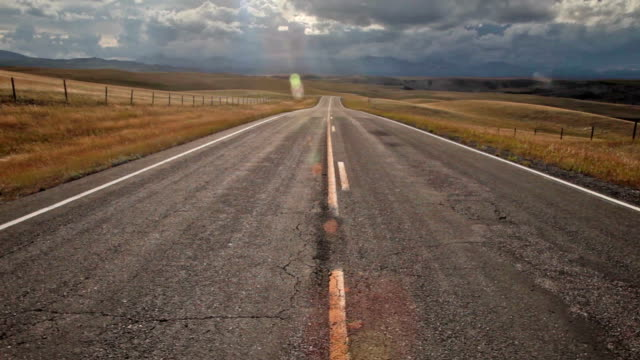 pov of empty highway with dramatic clouds on prairie and sun moving across landscape with pan down. and up. - 20秒或更長 個影片檔及 b 捲影像