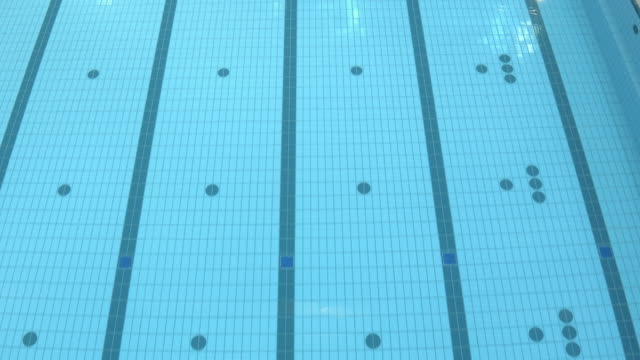 AERIAL Empty indoor swimming pool with blue and white tiles