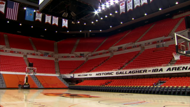 empty interior gallagheriba arena orange stadium seats lights on banners amp flags hanging from ceiling basketball court w/ oklahoma state university... - スポーツコート点の映像素材/bロール