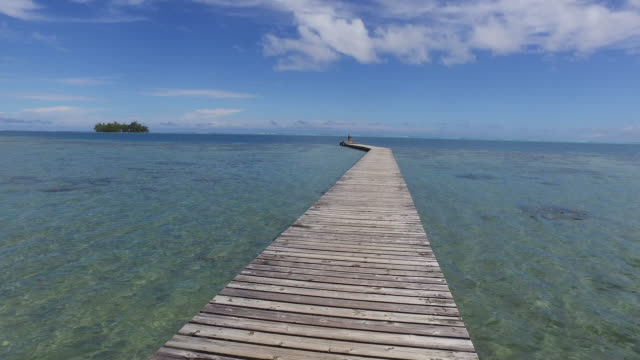 empty jetty leading to sea against sky - polynesian culture stock videos and b-roll footage