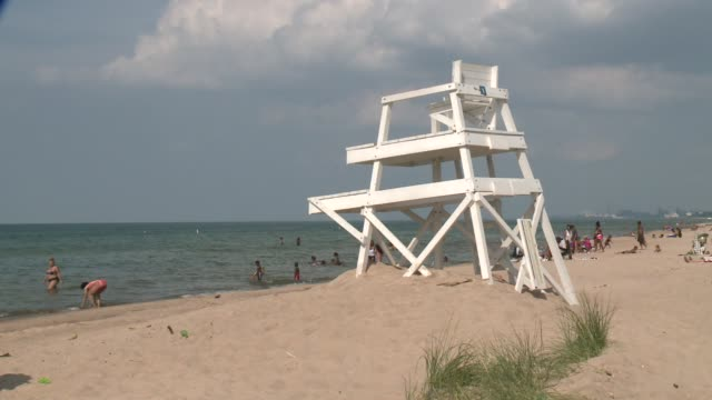 empty lifeguard stand at a populated beach on a sunny day in gary, indiana. - lifeguard chair stock videos & royalty-free footage
