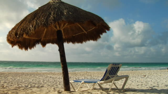 ws empty lounge chair on beach next to palapa blowing in wind / tulum, mexico - palapa stock videos & royalty-free footage