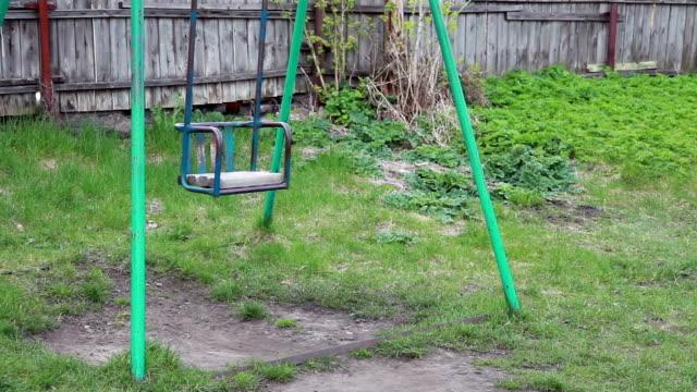 empty metal swing swaying in the backyard - negative emotion stock videos & royalty-free footage