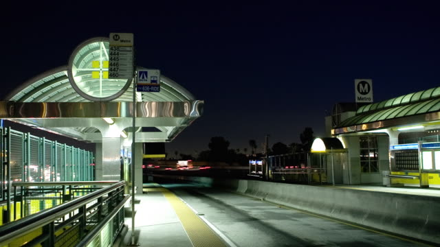 T/L MS Empty Metro bus station elevated on upper level Harbor 110 freeway with traffic passing by in background at night, Los Angeles, California, USA