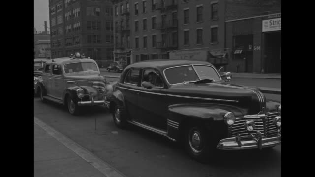 empty new york highway / over-shoulder shot man's hands hold stack of gasoline ration cards; he slaps them on his desk / very sparse traffic on... - world war ii video stock e b–roll