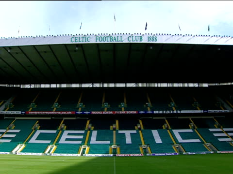 empty north stand of celtic park including green white and gold seats inscribed with celtic flags fly above celtic football club insignia on top of... - insignia stock videos and b-roll footage