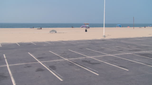 ws empty parking lot adjacent to a vacant beach / california, united states - car park stock videos & royalty-free footage