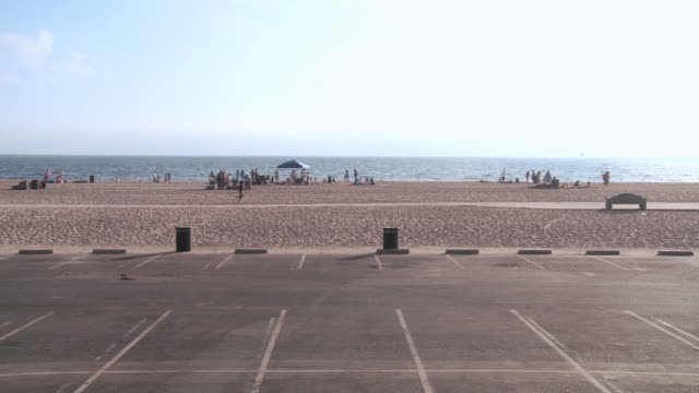 ha empty parking lot next to a quiet beach with bathers on a sunny day / seal beach, california, united states - parkfläche stock-videos und b-roll-filmmaterial