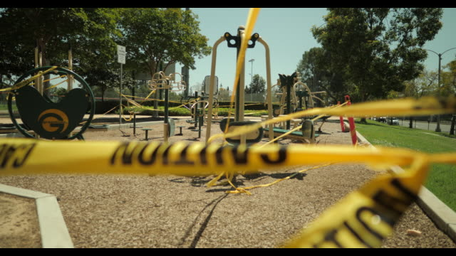 empty playground equipment wrapped in caution tape,  in closed public park during april 2020 covid-19 - loss stock videos & royalty-free footage