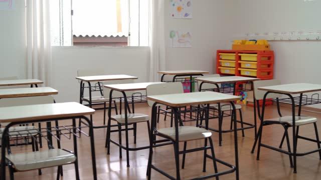 vidéos et rushes de salle de classe préscolaire vide avec des tables et des chaises - niveau primaire