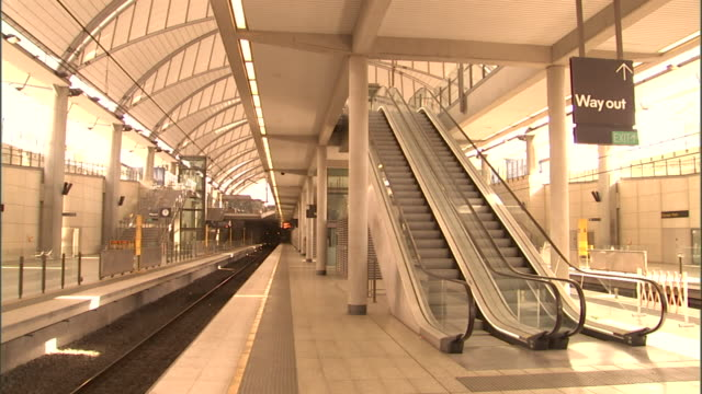 ms, empty railway station platform with moving escalators, olympic park railway station, sydney, australia - escalator stock videos & royalty-free footage