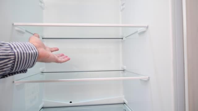 vídeos de stock e filmes b-roll de empty refrigerator. a man's hand shows it. - crise mundial de alimentos