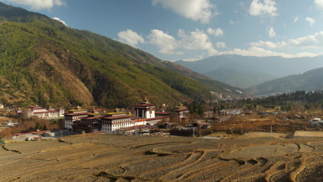empty rice fields in front of pan down onto tashichho dzong a buddhist monastery and fortress in thimphu capital of bhutan during winter time in... - thimphu stock videos & royalty-free footage