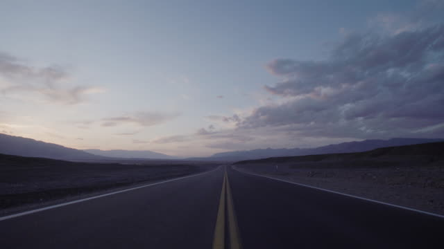 Empty road along the desert at sunset
