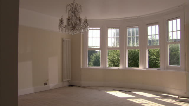 Empty room with open windows and chandelier hanging from ceiling