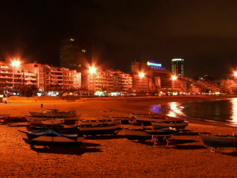 t/l ws empty rowboats on beach near waterfront hotels at night / las palmas de gran canaria, spain - unknown gender stock videos & royalty-free footage