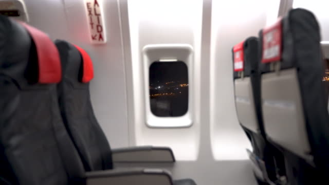 empty seats on the airplane and centered window with city lights visible outside while landing - vehicle interior stock videos & royalty-free footage