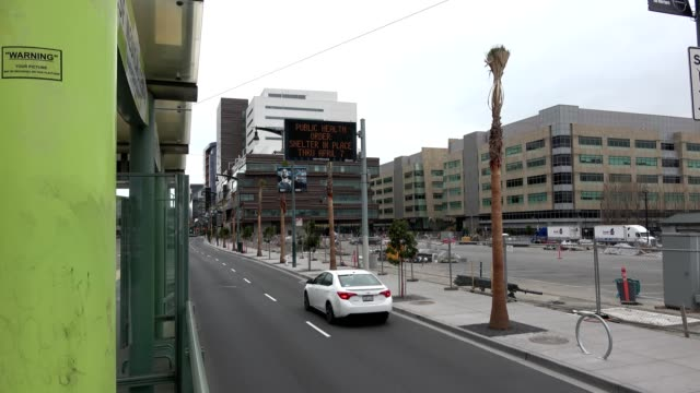 empty streets and electronic sign with lockdown messages are visible from a muni train station during an outbreak of the covid19 coronavirus san... - inquadratura fissa video stock e b–roll