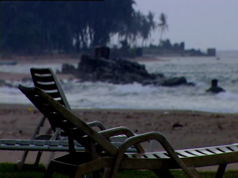 empty sunloungers on beach as waves lap onto shore sri lanka - outdoor chair stock videos & royalty-free footage