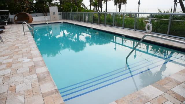 empty swimming pool overlooking beach - プールサイド点の映像素材/bロール